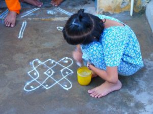 Child in India drawing a kolam floor painting
